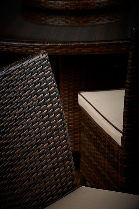brown rattan chair with table behind it